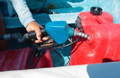 Man fueling tank of a motor boat before travel - stock photo