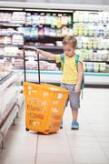 Stock Photo of Little boy with big shopping cart in the store