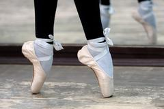 Close up view to ballerinas legs in pointes on wooden floor Stock Photos