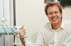 Laughing man with tousled hair holding dental tool - stock photo