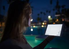 Woman tourist with pad on tropical resort in late evening - stock photo