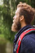 smiling man with beard and backpack hiking - stock photo