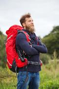 Stock Photo of smiling man with backpack and binocular outdoors