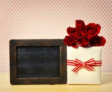 Present box with roses and blank chalkboard - stock photo