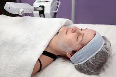 Beauty treatment of young female face, ozone facial steamer Stock Photos