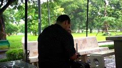Man waits rain under an umbrella in the park and uses phone. HD. 1920x1080 Stock Footage