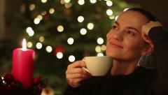 Happy young woman with coffee in front of Christmas tree HD Stock Footage