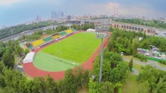 Rugby stadium against cityscape with traffic on bridge Stock Footage