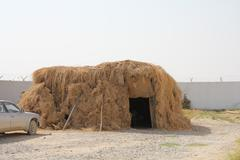 Afghanistan ethnic grass house with a car parked nearby - stock photo
