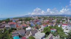 Aircraft flies above coastal town near mountains Stock Footage