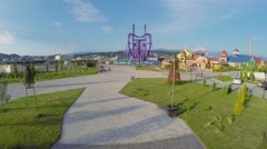 Tourists walk near Sochi-park at summer sunny day. Aerial view. Stock Footage