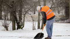 Worker with snow shovel in winter on sidewalk Stock Footage