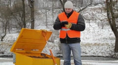 Worker with tablet PC on sidewalk near the sandbox Stock Footage