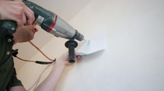 Worker is drilling a hole in the wall using an electric drill Stock Footage