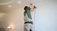 A man in overalls drills a hole in the wall in the new apartment Stock Footage