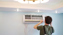 Stock Video Footage of Man unscrews the screw and remove the lid from air conditioner