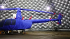 Helicopter covered with blue cover in the hangar of Heliport Stock Footage