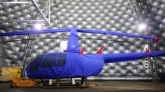Spacious hangar with a helicopter in the blue cover Stock Footage
