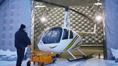 Man puts white helicopter in a hangar of Heliport Moscow Stock Footage