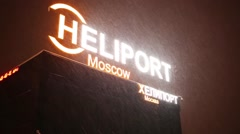 Heliport Moscow sign on roof of the building during a snowfall Stock Footage