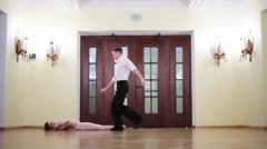Beautiful couple dancing in a room next to the door Stock Footage