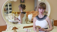 Beautiful girl stands near mirror with frame in hands Stock Footage
