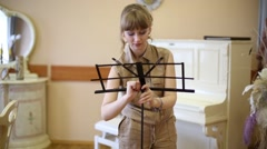 Beautiful girl installs music stand in room with classic interior Stock Footage
