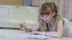 Beautiful girl in glasses sits at table and writes on paper Stock Footage