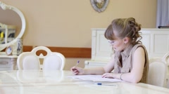 Stock Video Footage of Beautiful girl in glasses sits at table and writes on paper