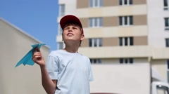 Boy in t-shirt launches paper airplane near residential building Stock Footage