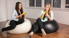 Stock Video Footage of Two girls sitting and eating big bananas
