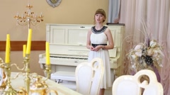 Pretty girl in white dress recites near white piano in light room - stock footage
