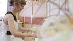 Happy girl in white dress plays white piano in light room - stock footage
