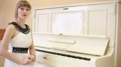 Beautiful girl in white dress speaks near white piano Stock Footage