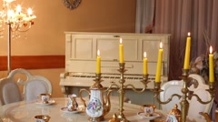 Table with set of porcelain dishes and lighted candles and lamp Stock Footage