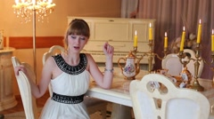 Beautiful girl in dress sits at table with porcelain and speaks Stock Footage