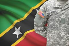 American soldier with flag on background - Saint Kitts and Nevis Stock Photos