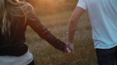 Stock Video Footage of Young couple in love holding hands walking in field at sunset. Slow motion