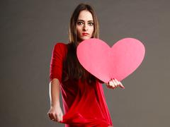 Woman in red dress holds heart sign - stock photo