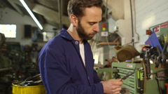 Mechanic repairing some part of an engine in an auto repair shop - stock footage