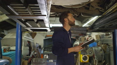 Mechanic inspects the car undercarriage way and makes a note Stock Footage