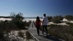 Couple walking along boardwalk to beach Stock Footage