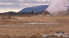 Iceland, Namaskard, Couple Walks through Geyser Field Stock Footage