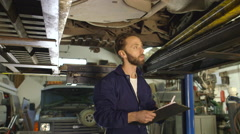Mechanic inspects the car undercarriage way and taking notes Stock Footage