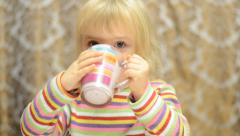 Little girl drinks emotionally and sign thumb up Stock Footage
