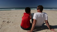 Couple sitting and relaxing on beach looking at ocean - stock footage