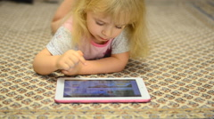 Baby Girl Playing on Tablet Computer Lying on Carpet - stock footage