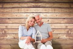 Stock Photo of Composite image of happy couple sitting and holding house outline