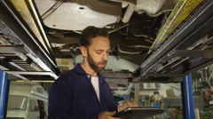 Mechanic inspects the car undercarriage way with a digital tablet Stock Footage