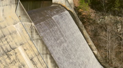 Overflow water from lake spills over dam Stock Footage